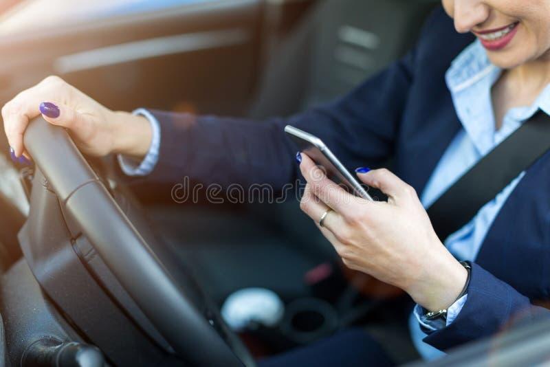 Γυναίκα που χρησιμοποιεί το smartphone οδηγώντας ένα αυτοκίνητο στοκ εικόνες με δικαίωμα ελεύθερης χρήσης
