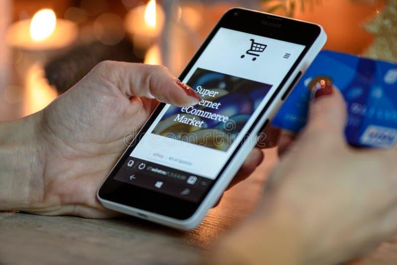 Πρόσωπο που χρησιμοποιεί τη γραπτή μπλε κάρτα Smartphone και εκμετάλλευσης στοκ φωτογραφίες με δικαίωμα ελεύθερης χρήσης