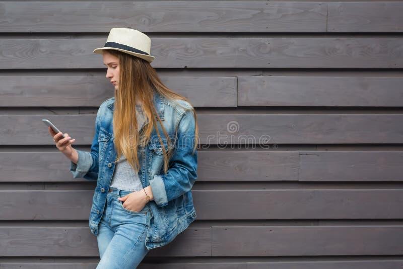 Smartphone adolescente da mulher fora da parede de madeira imagem de stock