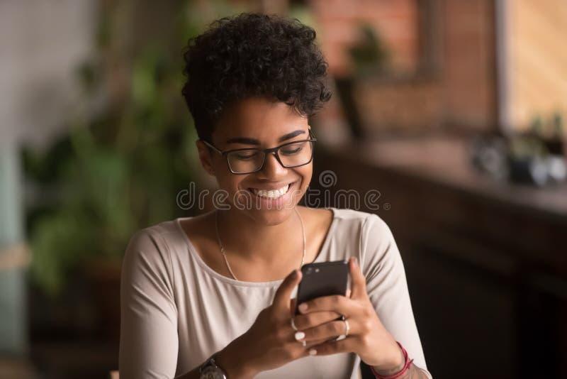 Smartphone afroamericano millenario felice della tenuta della donna facendo uso dei apps di commercio elettronico fotografia stock libera da diritti