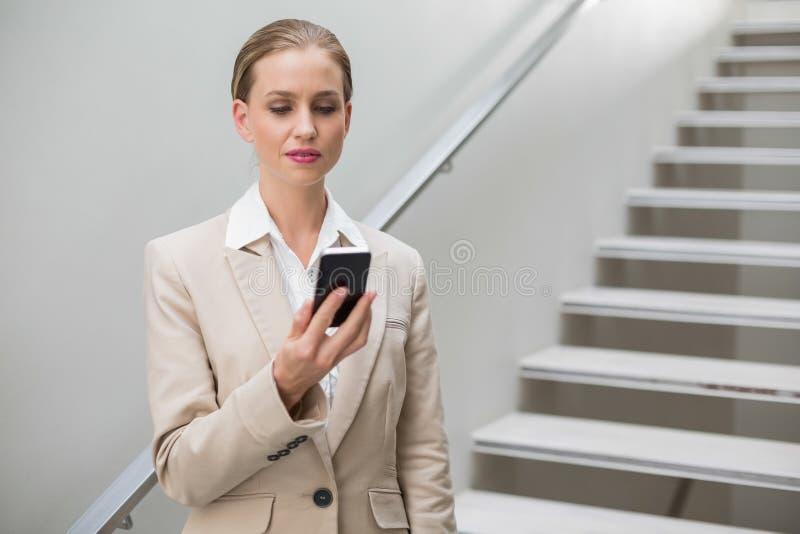 Smartphone alla moda premuroso della tenuta della donna di affari immagine stock libera da diritti