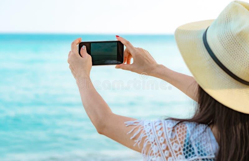 Smartphone asiático do uso do chapéu do desgaste de mulher do moderno que toma a foto do mar bonito Férias de verão na praia trop imagem de stock royalty free