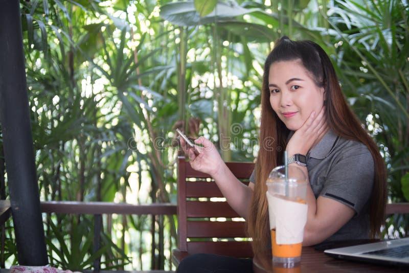 Smartphone asiático hermoso del control de la mujer y mirada de la cámara, revestimiento foto de archivo