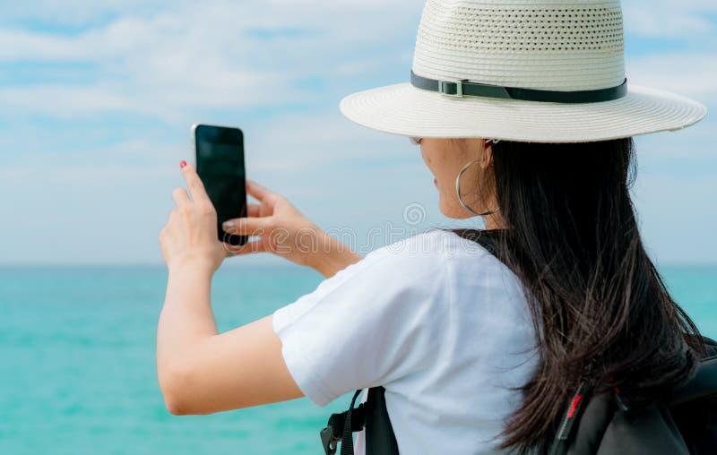 Smartphone asiático joven del uso del sombrero del desgaste de mujer del backpacker que toma el selfie en el embarcadero Vacacion fotografía de archivo libre de regalías