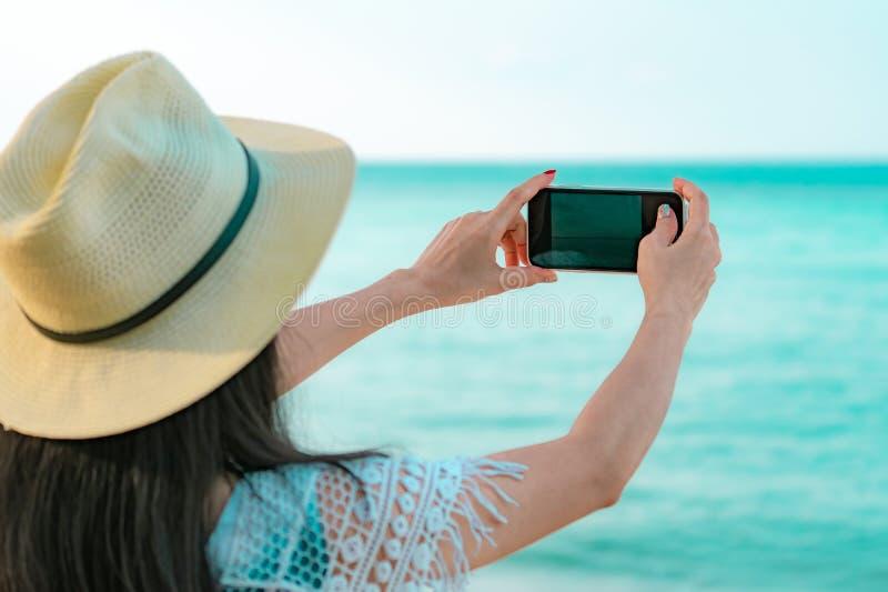 Smartphone asi?tico novo do uso do chap?u do desgaste de mulher que toma a foto na praia tropical F?rias de ver?o na praia tropic fotografia de stock