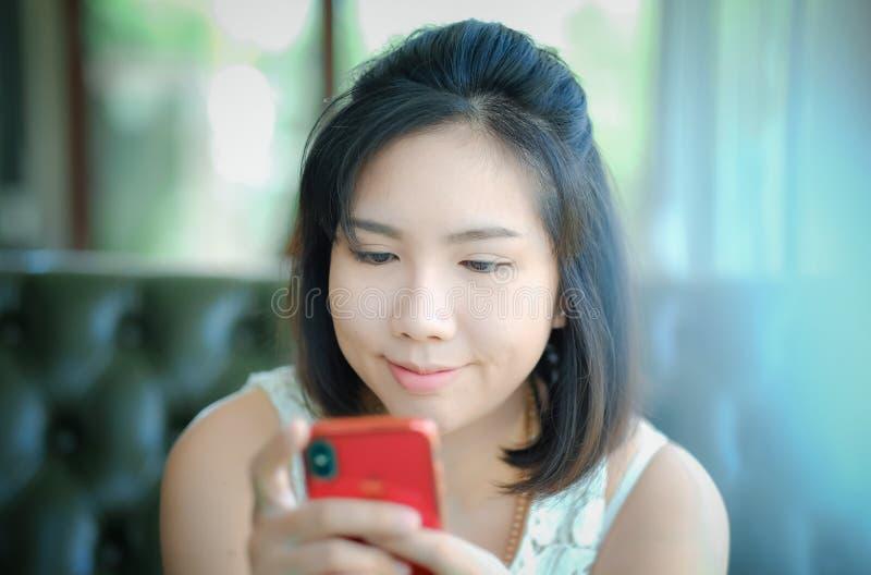 Smartphone asiático novo do uso da mulher, menina de Tailândia imagens de stock royalty free