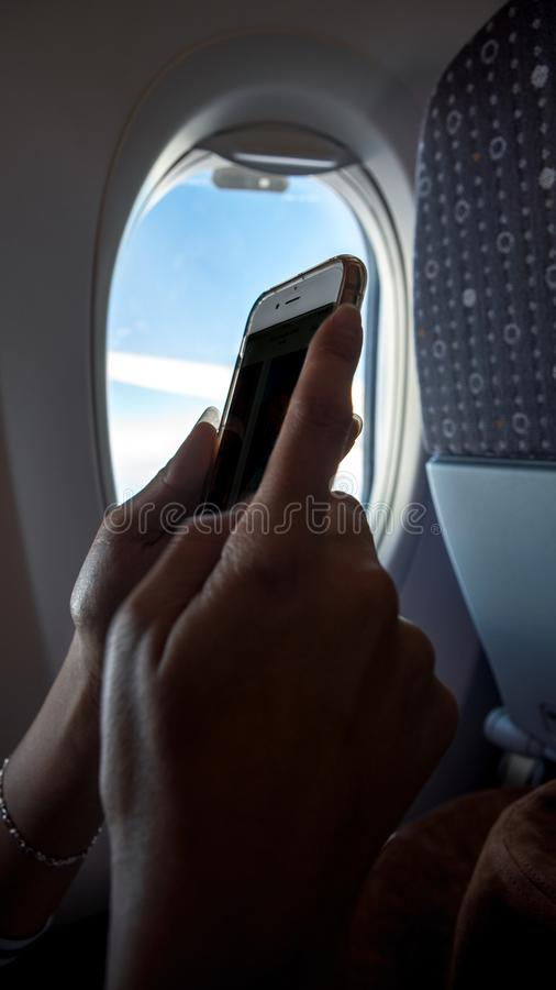 Smartphone asiatico della tenuta della donna durante il viaggio di volo Viaggiatore sull'aereo fotografia stock libera da diritti