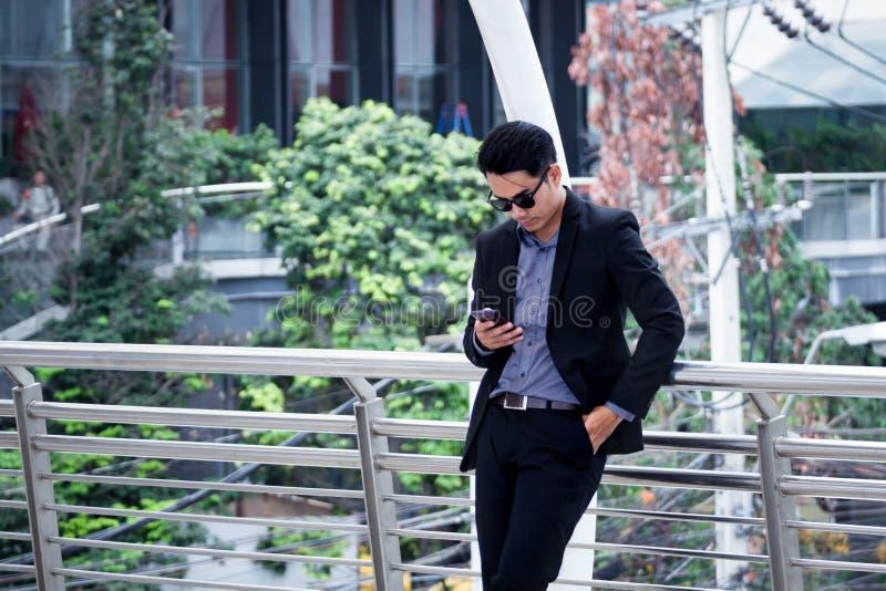 Smartphone asiatico di condizione e di uso dell'uomo di affari con il bui di affari fotografia stock libera da diritti