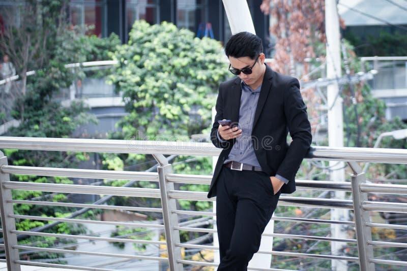 Smartphone asiatico di condizione e di uso dell'uomo di affari con il bui di affari immagini stock libere da diritti