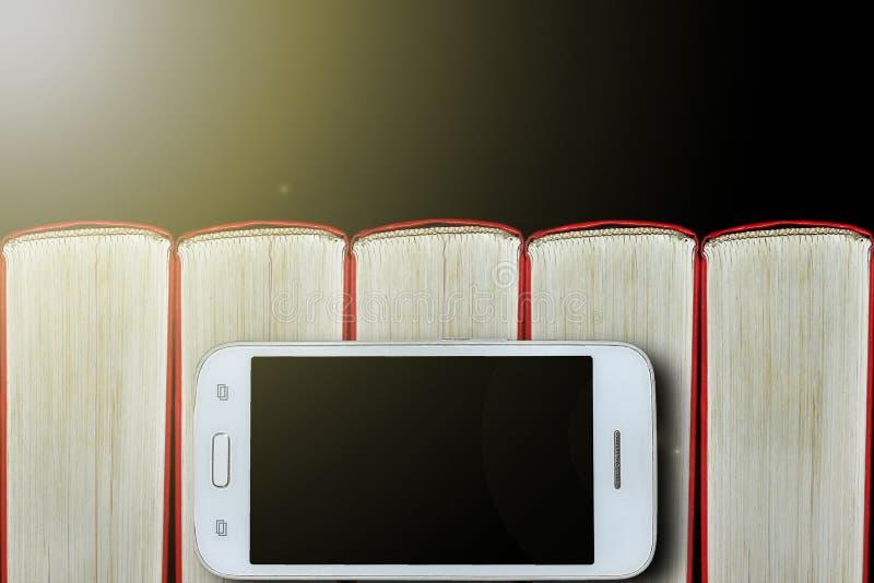Smartphone auf dem Hintergrund von Büchern Dunkler Hintergrund, Exemplarplatz Konzept: Bücher und elektronische Geräte stockfoto