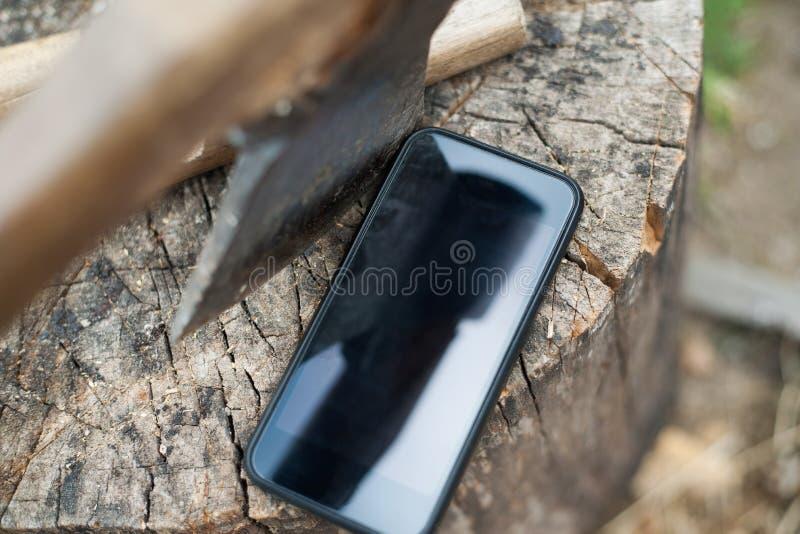 Smartphone auf dem Stumpf Smartphone nahe der Axt Handy und Axt auf Baumstamm stockfotos