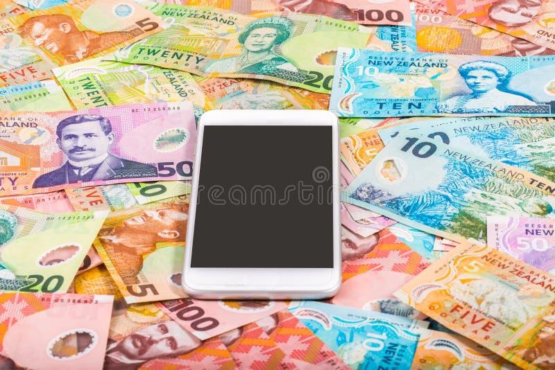 Smartphone auf Geldhintergrund stockfoto