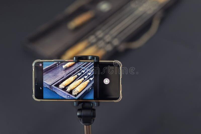 Smartphone auf Stativschie?engegenst?nden am Innenfotostudio Berufsgegenstandphotographie mit Telefon Erwerben des Geldes mit stockbild