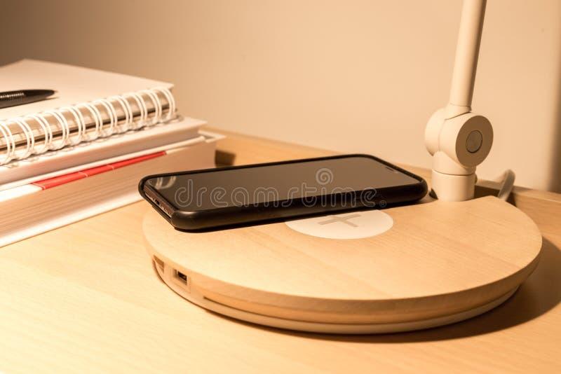 Smartphone in Aufladungsradioapparat des schwarzen Kastens auf Betttabelle lizenzfreies stockfoto