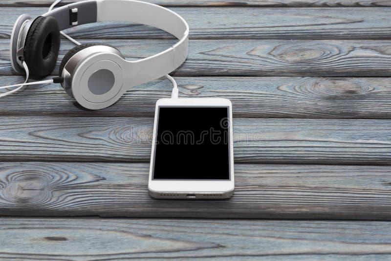 Smartphone, auriculares en un fondo de madera fotos de archivo
