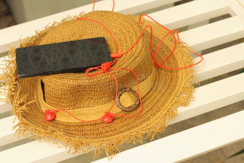 Smartphone avec l'écouteur, chapeaux de paille photographie stock libre de droits