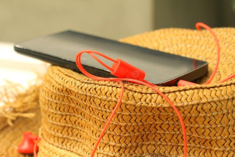 Smartphone avec l'écouteur, chapeaux de paille photos libres de droits