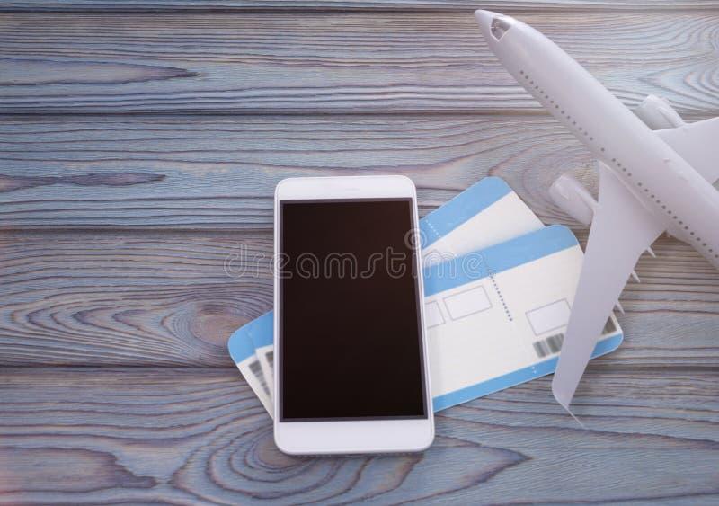 Smartphone avec l'écran noir, billets d'avion sur un fond en bois photos libres de droits