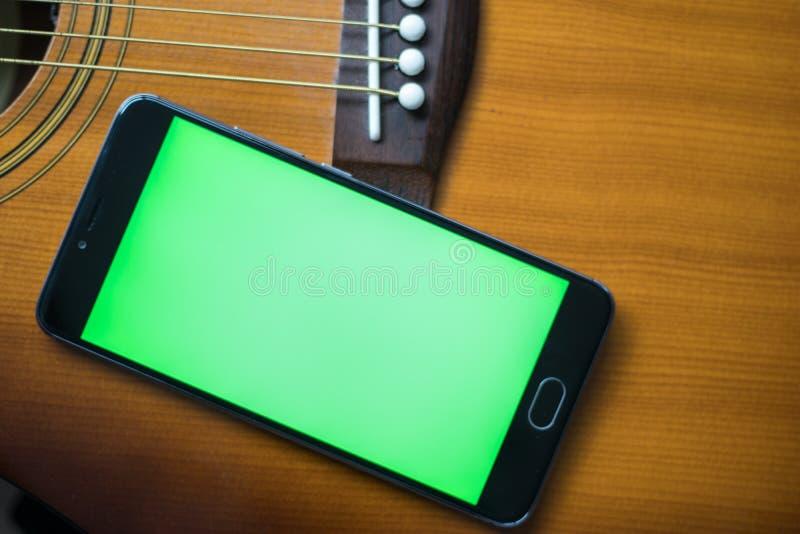 Smartphone avec l'écran vert sur une guitare acoustique photos libres de droits