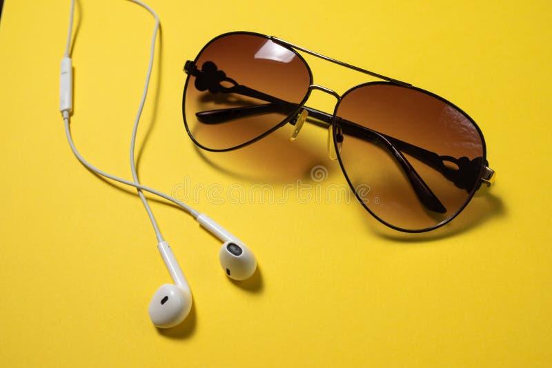 Smartphone avec l'écran vide se relie aux écouteurs au câble en spirale sur la vue supérieure de fond jaune, lunettes de soleil photo stock