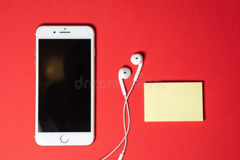 Smartphone avec l'écran vide se relie aux écouteurs au câble en spirale sur la vue supérieure de fond rouge images libres de droits