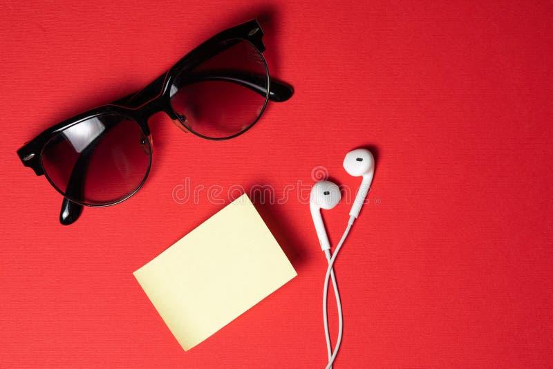 Smartphone avec l'écran vide se relie aux écouteurs au câble en spirale sur la vue supérieure de fond rouge, lunettes de soleil photos stock