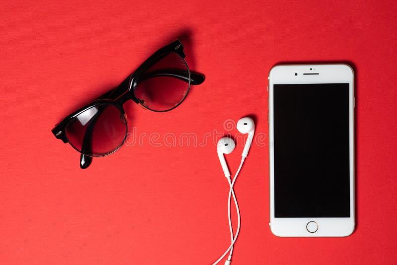 Smartphone avec l'écran vide se relie aux écouteurs au câble en spirale sur la vue supérieure de fond rouge, SunglassesÑŽ image libre de droits