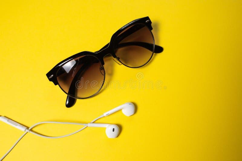 Smartphone avec l'?cran vide se relie aux ?couteurs au c?ble en spirale sur la vue sup?rieure de fond jaune, lunettes de soleil photos libres de droits