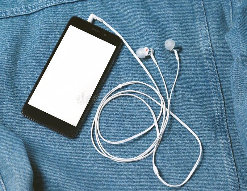 Smartphone avec la caisse noire et un écran blanc vide et branchés des earbuds d'écouteurs sur le fond du denim photos stock