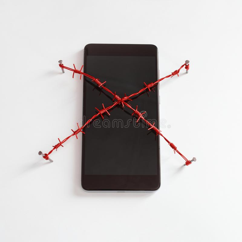 Smartphone avec le barbelé rouge Concept pour le thème de la dépendance humaine à l'égard les réseaux sociaux et l'Internet photo stock
