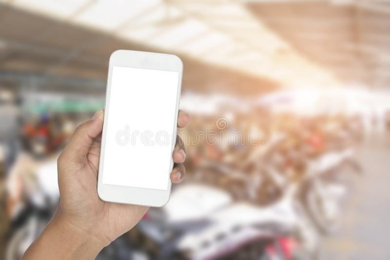 Smartphone avec le stationnement de voiture de fond de tache floue ou le stationnement de moto photographie stock