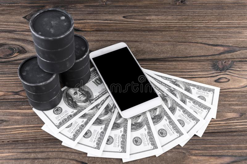 Smartphone, barrels of oil, dollars. On the background of a wooden table. fuel industry. purchase, sale stock photo