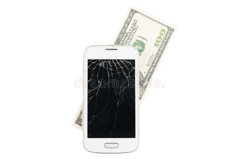 Smartphone bianco rotto con soldi nei precedenti fotografia stock libera da diritti