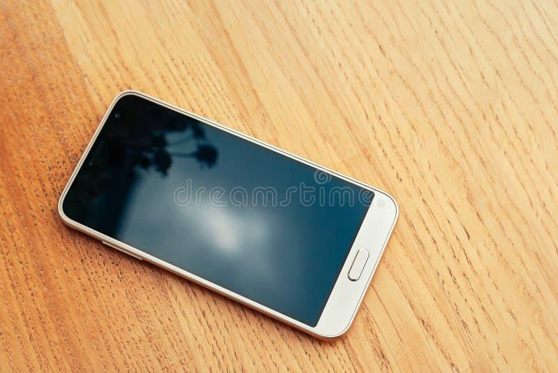 Smartphone bianco su struttura di legno del fondo della tavola con lo PS della copia immagini stock