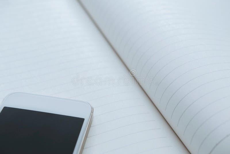 Smartphone bianco sul taccuino, spazio della copia fotografia stock libera da diritti