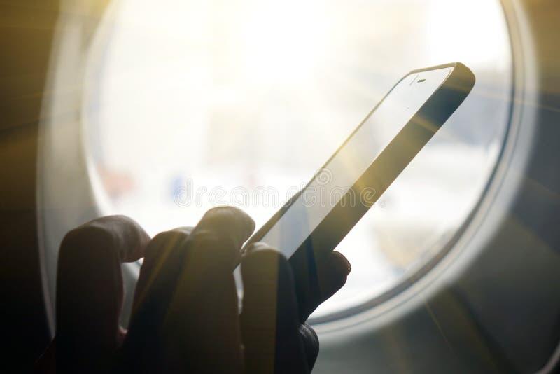 Smartphone bij het venster Bedrijfstechnologie en het concept reisideeën royalty-vrije stock fotografie