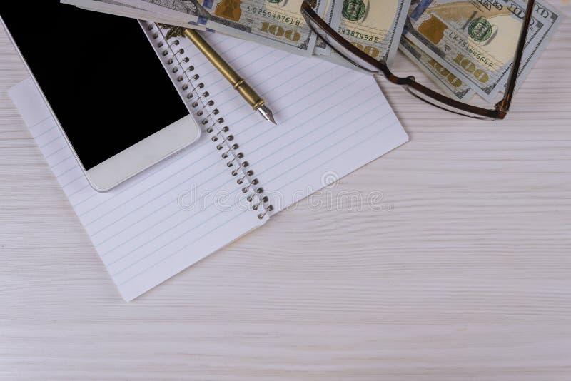 Smartphone, billetes de banco del dólar de papel al lado de una pluma y de los vidrios fotografía de archivo libre de regalías