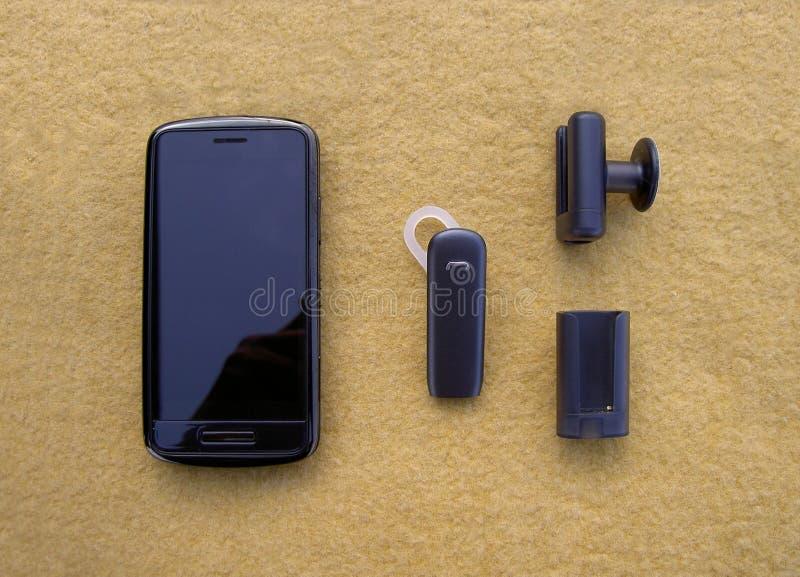 Smartphone black, bluetooth handsfree headset and holders stock image
