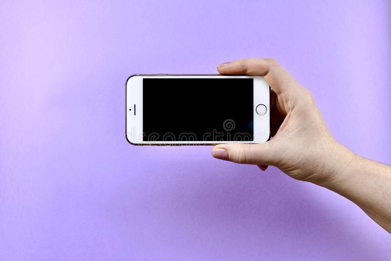 A smartphone with a black screen is turned off in the brush of one outstretched hand, on a purple background. Mobile phone, smartphone with a black screen off royalty free stock images