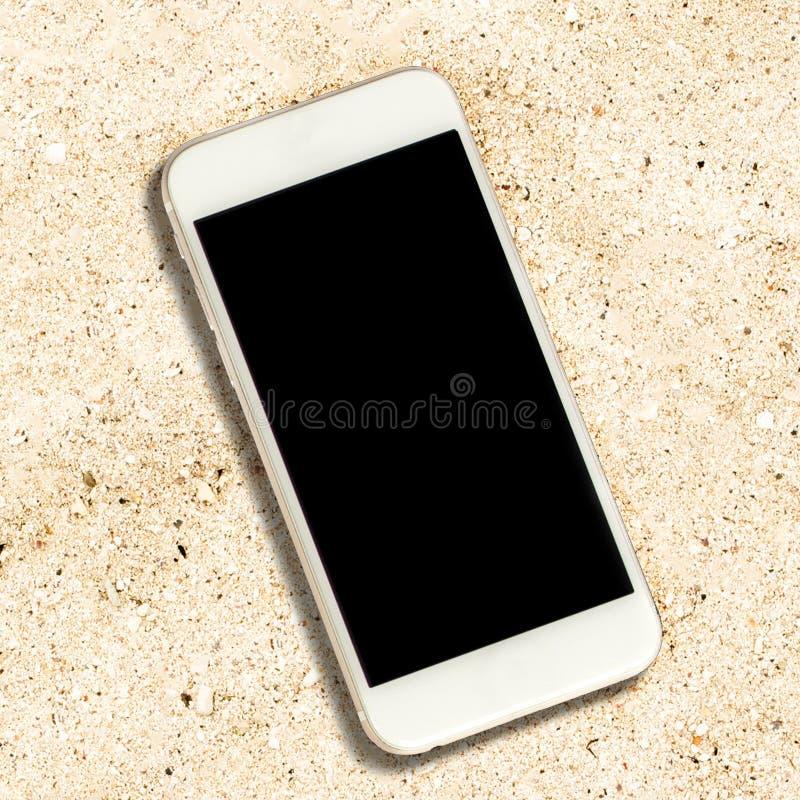 Smartphone blanc avec l'écran noir sur le fond blanc de sable images stock