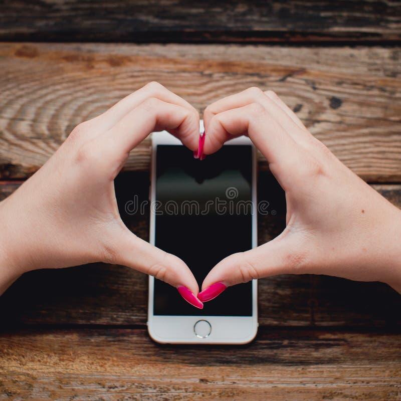Smartphone blanc dans des mains femelles sur un fond en bois photographie stock libre de droits