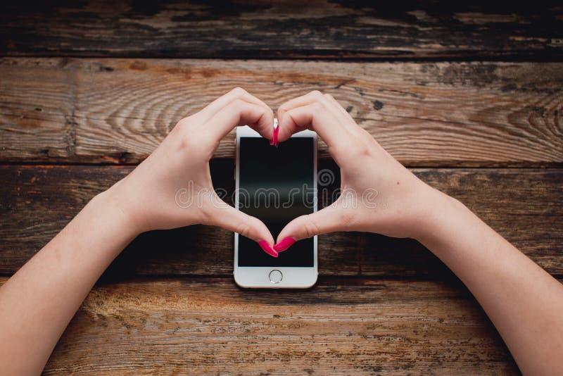 Smartphone blanc dans des mains femelles sur un fond en bois image stock