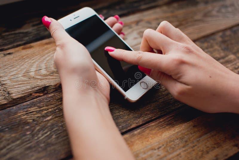 Smartphone blanc dans des mains femelles sur un fond en bois images stock