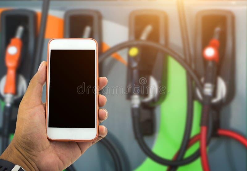 Smartphone blanc de prise masculine de main et vérification du prix de carburant sur le gaso images stock