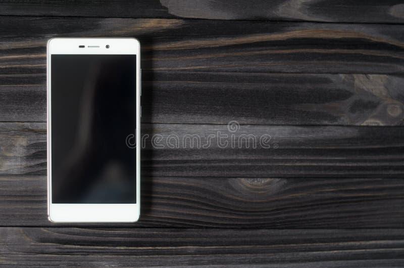 Smartphone blanc sur la table en bois foncée photographie stock