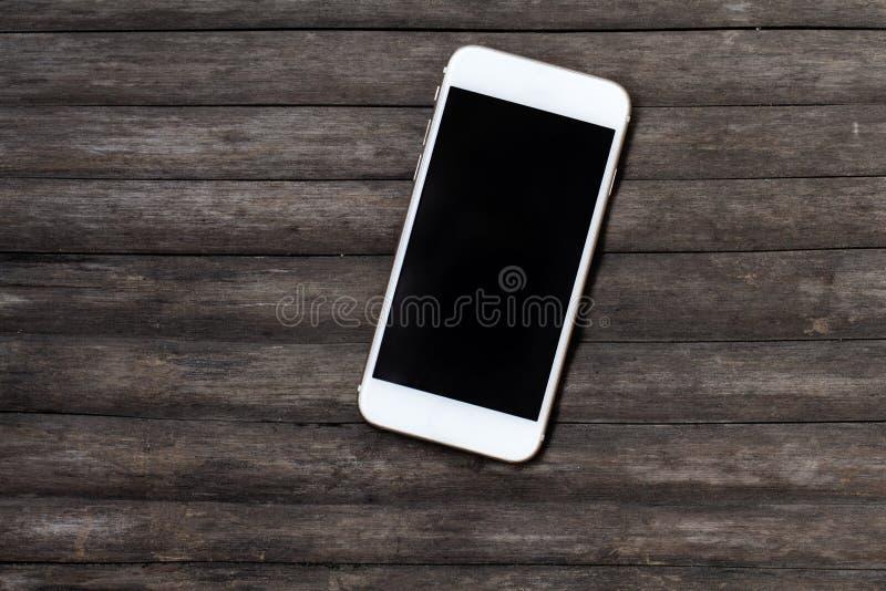 Smartphone blanc sur la table en bois foncée Smartphone noir d'écran sur le fond chic minable photographie stock libre de droits