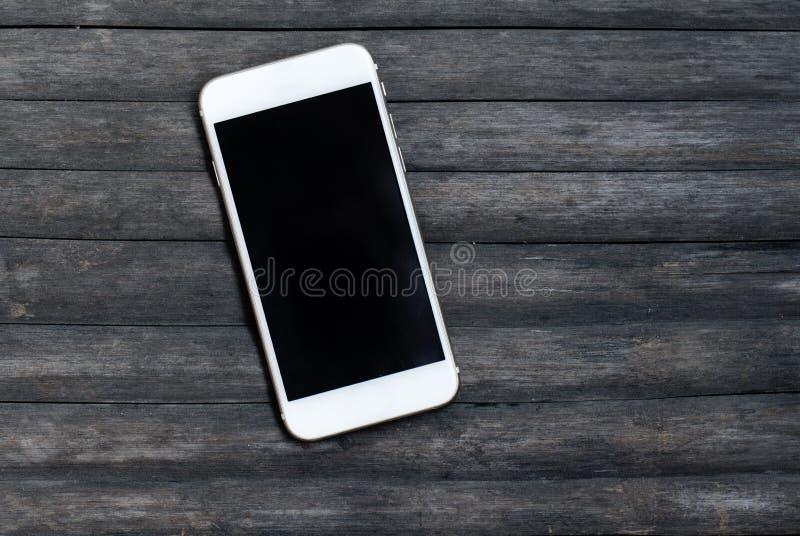 Smartphone blanc sur le fond en bois gris Maquette personnelle de dispositif images libres de droits