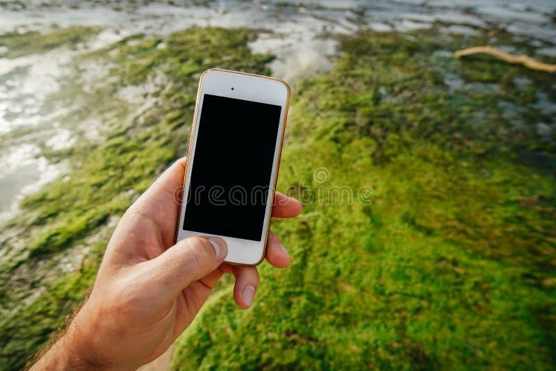 Smartphone blanco del teléfono en la mano de un hombre con una pantalla negra vacía en el fondo de la costa costa durante la baja fotos de archivo libres de regalías