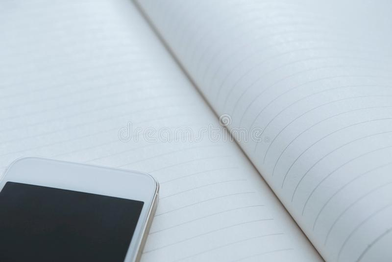 Smartphone blanco en el cuaderno, espacio de la copia fotografía de archivo libre de regalías