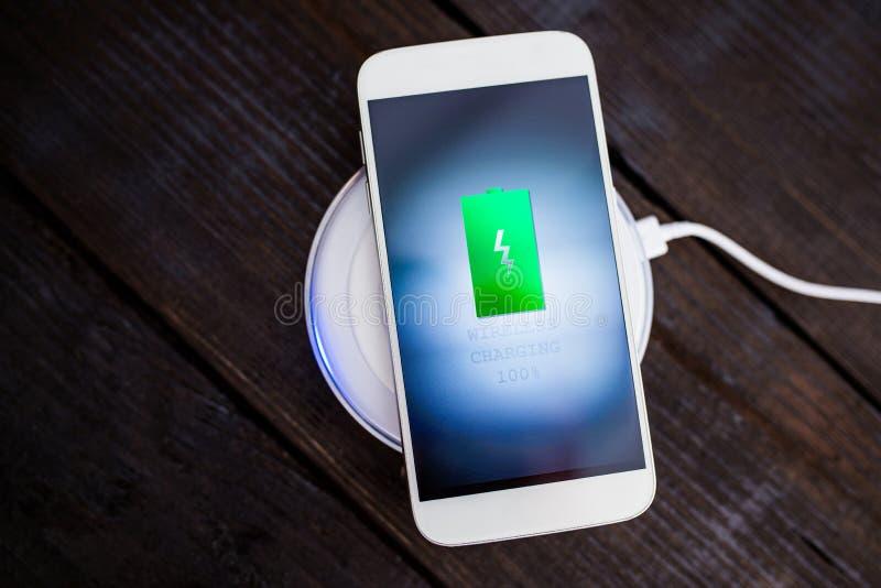 Smartphone blanco que carga en un cojín de carga fotos de archivo libres de regalías